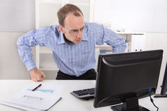 Computer crash: shocked manager in blue shirt in front of his co Royalty Free Stock Photography