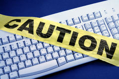 Computer crime. Plastic caution tape and keyboard, computer crime royalty free stock image