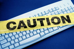 Computer crime. Plastic caution tape and keyboard, computer crime Stock Photos