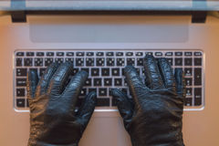 Computer crime. Metaphor, hand in black gloves on a computer stock photos