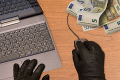 Computer crime methaphor. Computer crime metaphor, hand in black gloves with mouse, computer and banknotes royalty free stock images