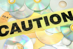 Computer crime pirate. Plastic caution tape and CD, computer crime royalty free stock images