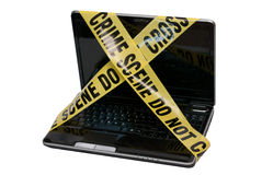 Computer Crime Scene. A laptop computer is wrapped in yellow police tape reading Crime Scene Do Not Cross. The concept represents compromised computer systems Royalty Free Stock Images
