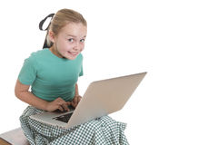 Computer cuteness. Young girl with a computer on her lap, giving a very cheeky smile to the camera Royalty Free Stock Photos