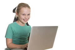 Computer cuteness. Young girl with a computer on her lap, smiling at the camera Royalty Free Stock Image