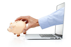 Computer Cyber Crime Security. A hand reaching out of the computer screen to grab a piggy bank isolated on a white background Royalty Free Stock Photo