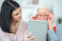Computer d'aiuto della compressa di uso della donna anziana Fotografie Stock