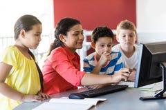 computer d'istruzione dell'insegnante femminile ai bambini Fotografia Stock Libera da Diritti