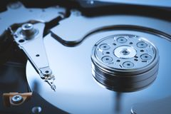 Computer data storage hard disk drive head stack parts electronic device technology blue background closeup stock photography