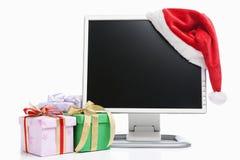 Computer, de hoed van de Kerstman en giften stock foto's