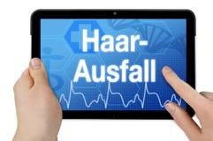 Computer della compressa con la parola tedesca per perdita di capelli - Haarausfall fotografia stock libera da diritti