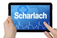 Computer della compressa con la parola tedesca per scarlattina - Scharlach fotografia stock libera da diritti