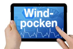 Computer della compressa con la parola tedesca per varicella - Windpocken fotografia stock libera da diritti