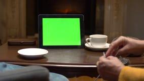 Computer della compressa del modello di Greenscreen sulla tavola con la tazza di caffè in caffè archivi video