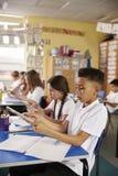 Computer della compressa di uso dei bambini nella classe di scuola primaria, verticale immagini stock