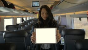 Computer della compressa della tenuta della giovane donna mentre viaggiando in treno stock footage