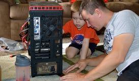 Computer della riparazione del figlio e del padre immagini stock