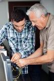 Computer della riparazione di And Senior Man dell'istitutore nella classe Fotografia Stock Libera da Diritti