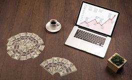 Computer desk with laptop and red arrow chart in screen Stock Photo