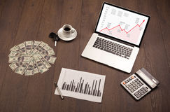 Computer desk with laptop and red arrow chart in screen Stock Image