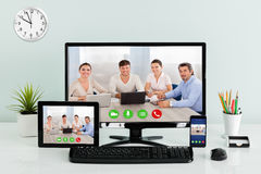Computer Desktop With Digital Tablet And Mobilephone On Desk. Computer Desktop With Digital Tablet And Mobilephone Showing Videoconferencing Application On Royalty Free Stock Photography