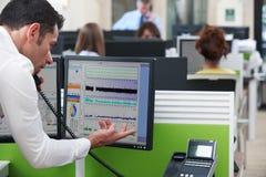 Computer di On Phone Using dell'uomo d'affari in ufficio occupato fotografia stock