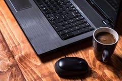 Computer di punta del rivestimento di Sideview con il topo e la tazza di caffè senza fili Fotografia Stock