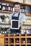 Computer di Showing Blank Tablet del rappresentante nel negozio di vino Fotografia Stock Libera da Diritti