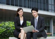Computer di uso della donna di affari con l'uomo d'affari Fotografia Stock Libera da Diritti