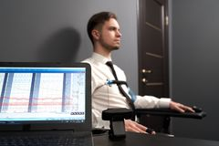 Computer with diagrams for pulse indicating on lie test. Selective focus of computer with diagrams for pulse indicating. Man sitting on chair and answering royalty free stock photo