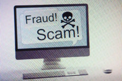 Computer displaying internet fraud and scam warning on screen. Desktop computer displaying conceptual internet fraud and scam warning on screen royalty free stock photography