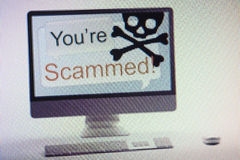 Computer displaying internet fraud and scam warning on screen Royalty Free Stock Photos