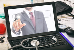 Computer on a doctor`s desk. Laptop`s screen showing a man in suit royalty free stock photos