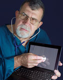 Computer Doctor with Stethoscope. A doctor listens with a stethoscope to the workings of a broken computer display Royalty Free Stock Photo