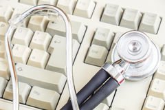Computer doctor. Stethoscope lying on a computer keyboard - for concepts like online medical help, computer repairs or computer diagnostics - selective focus is stock photo