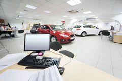 Computer and documents on wooden table and new cars. Stand in office of car shop Stock Photo