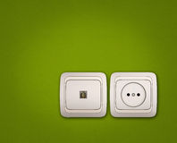 Computer and electrical outlets on green wall Stock Image
