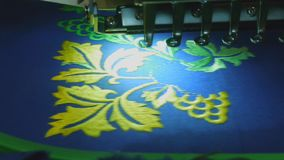 Computer embroidery machine makes bright patterns on a blue, close up stock footage