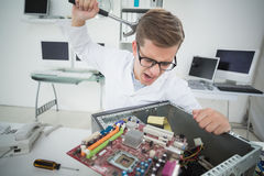 Computer engineer holding hammer over broken console Stock Photography