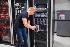 Computer Engineer Installing Server Into Blade Enclosure. Mid adult male computer engineer installing server into blade enclosure in datacenter Stock Photography