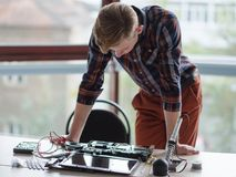 Computer engineer laptop science technology design. Computer engineer standing over a disassembled laptop. Science technology electronics design development Stock Image