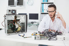 Computer engineer looking at broken device and making a phone call Stock Image