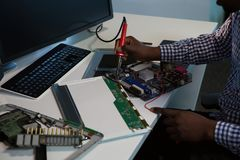 Computer engineer repairing motherboard at desk. In office Royalty Free Stock Images