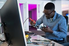 Computer engineer repairing motherboard at desk. In office Stock Images