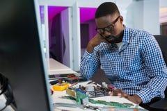 Computer engineer repairing motherboard at desk. In office Stock Photos