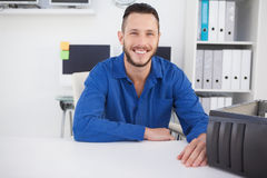 Computer engineer sitting at desk smiling at camera Royalty Free Stock Photos