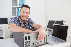 Computer engineer smiling at camera beside open console Stock Image