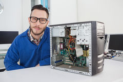 Computer engineer smiling at camera beside open console Stock Images