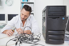 Computer engineer working on broken cables. In his office Stock Image