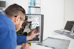 Computer engineer working on broken console with screwdriver. In his office Stock Image